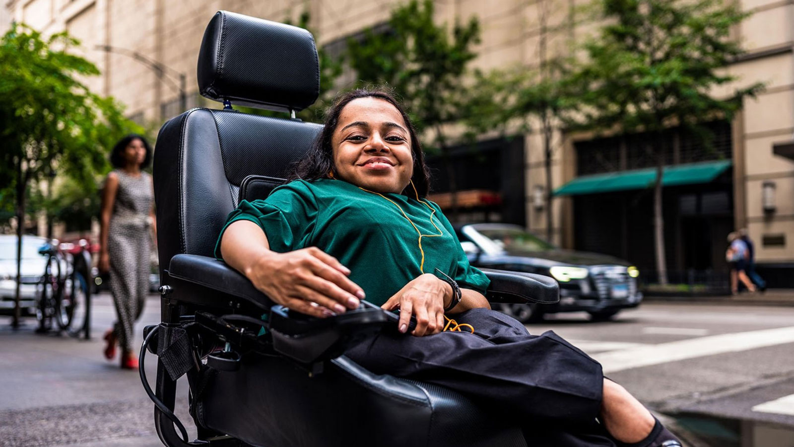 A young professional women with a big smile who is a power wheelchair user is crossing the street in a busy city.